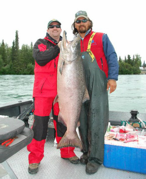 two fishmen hold up large king salmon caught on the kenai river