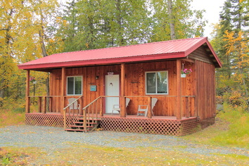 Cabin at Alaska Hooksetters Lodge in Kenai with trees and fire pit