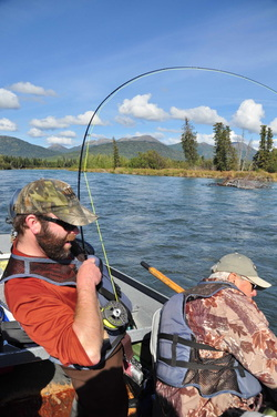 Men fly fishing from drift boat on Kenai River