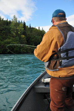 Fisherman fishing from drift boat on Kenai River