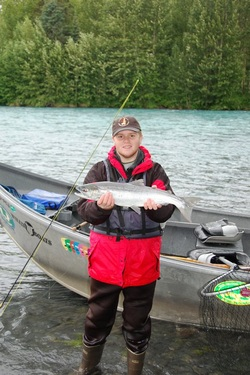 young fisherman holds up silver salmon next to drift boat on Kenai River