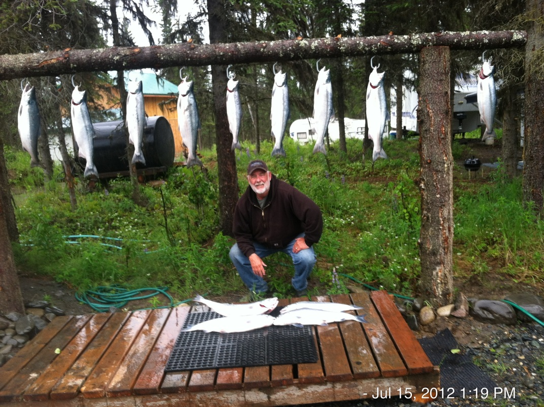 Fishing guide outside lodge with rack of red salmon caught by guests on a charter.