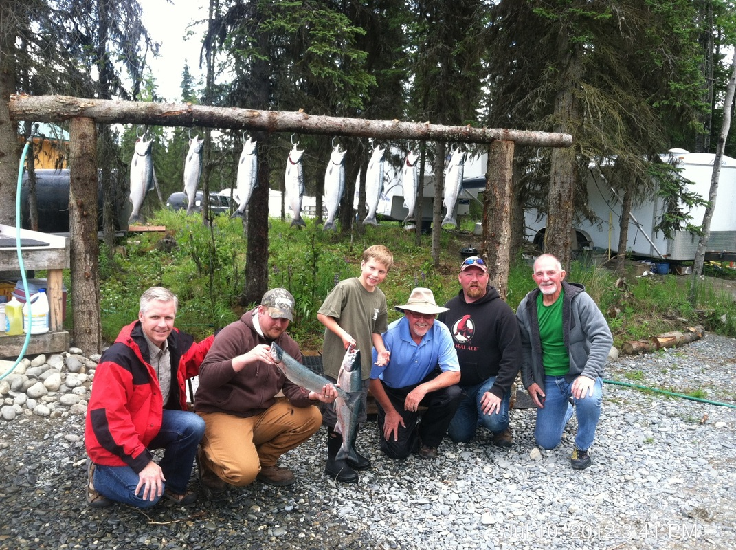 Lodge guests smile after a memorable fishing charter on Alaska rivers.