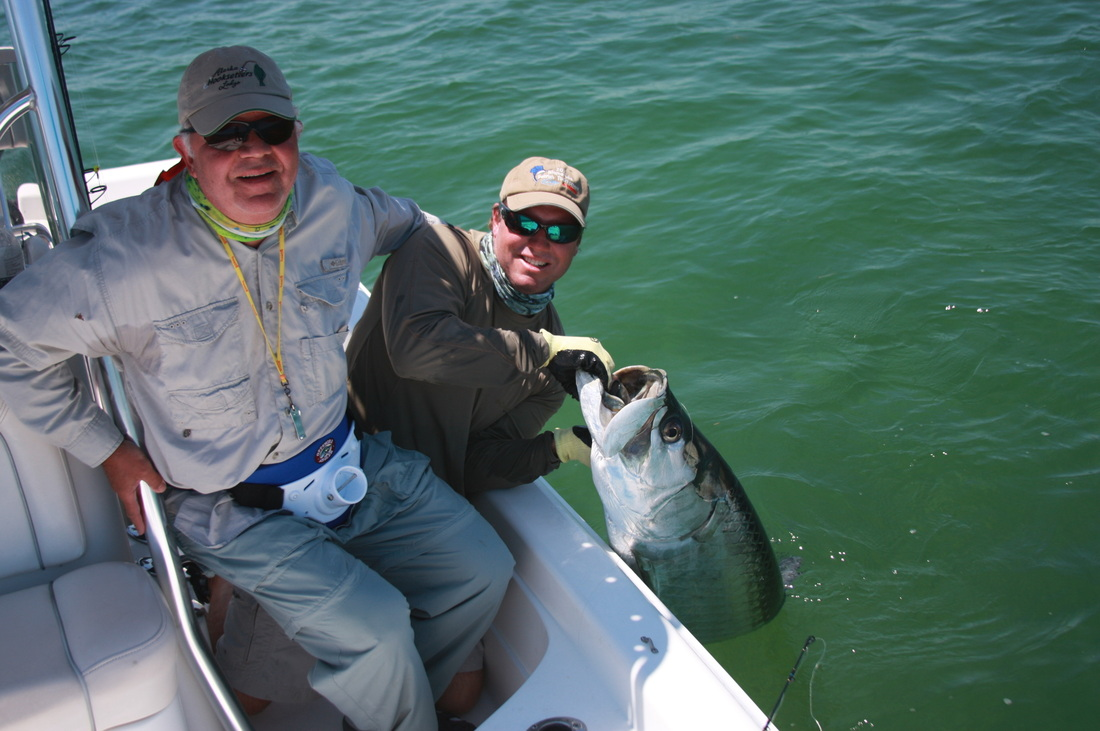 Fisherman and guide with large tarpon caught and released in Florida.