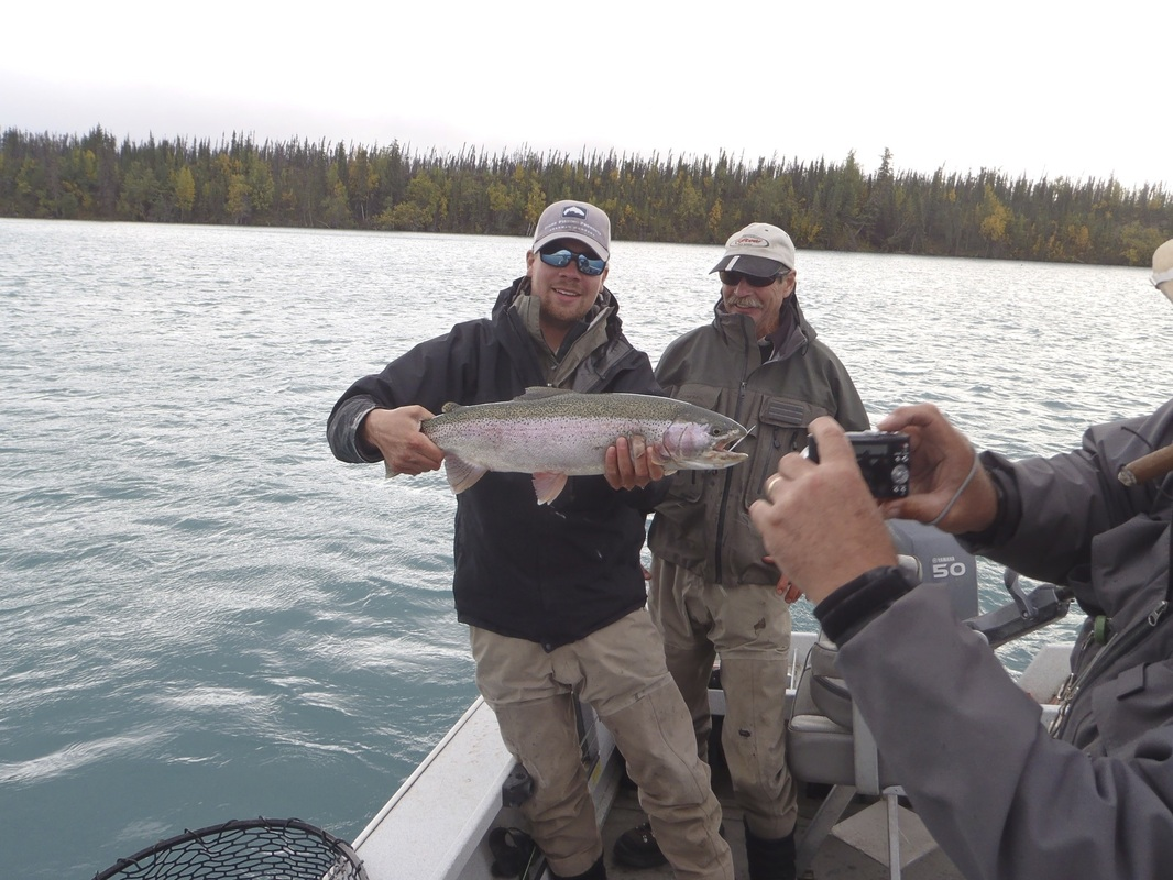 Lodge guests pose with their trout catch while out on a fishing charter.